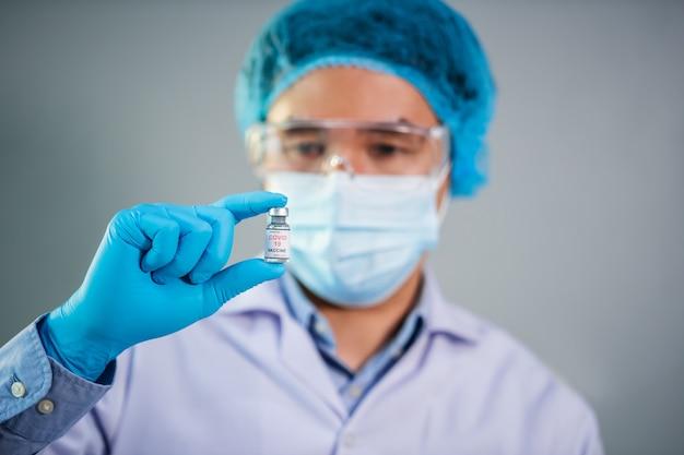 Männlicher arzt mit coronavirus (covid-19) -impfstoffflasche für injektionsmedizin