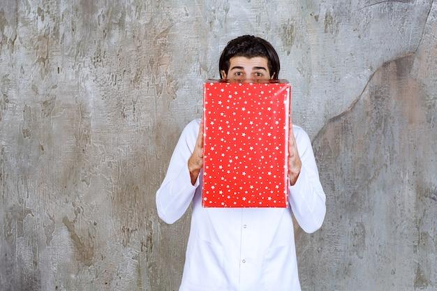 Männlicher arzt mit einem stethoskop, das eine rote geschenkbox hält und verwirrt und begeistert aussieht.