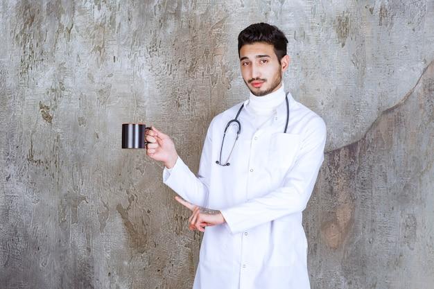 Männlicher arzt mit stethoskop, das eine tasse kaffee hält.