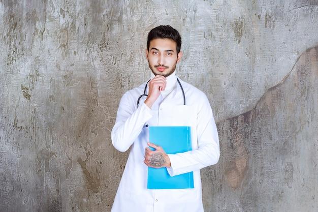 Männlicher arzt mit stethoskop, das einen blauen ordner hält, denkend und planend.