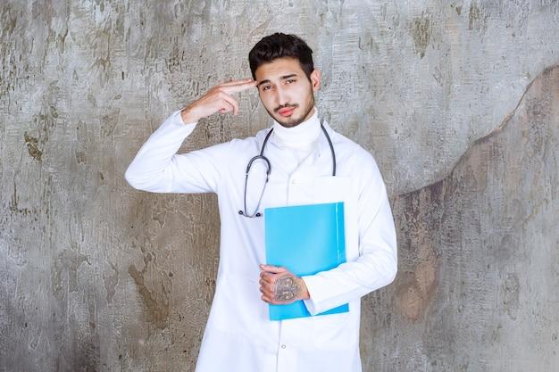 Männlicher arzt mit stethoskop, das einen blauen ordner hält, denkt und plant.
