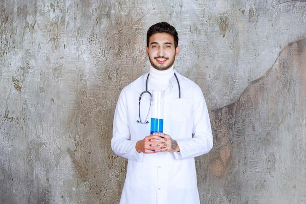 Männlicher arzt mit stethoskop, der eine chemische flasche mit blauer flüssigkeit im inneren hält
