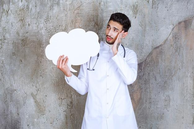 Männlicher arzt mit stethoskop, der eine leere wolkenform-infotafel hält und nachdenklich aussieht.