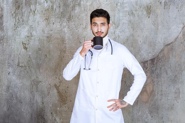 Männlicher arzt mit stethoskop, der eine tasse kaffee hält und ihn trinkt