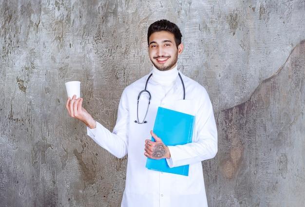 Männlicher arzt mit stethoskop, der eine tasse und einen blauen ordner hält