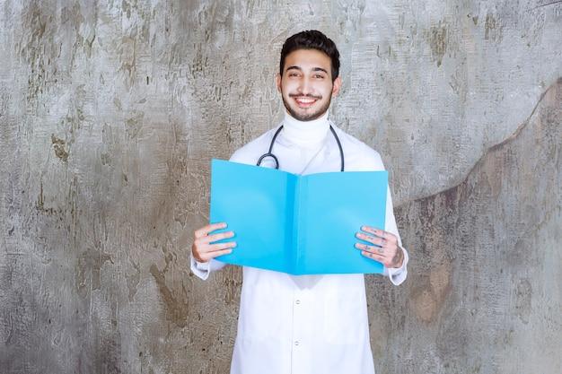 Männlicher arzt mit stethoskop, der einen blauen ordner hält