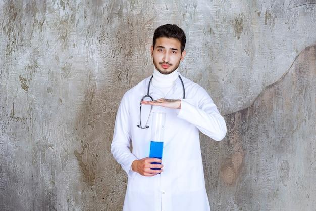 Männlicher arzt mit stethoskop, der einen chemischen kolben mit blauer flüssigkeit nach innen hält.