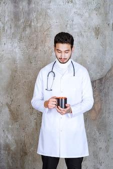 Männlicher arzt mit stethoskop hält eine tasse kaffee und wärmt die hände
