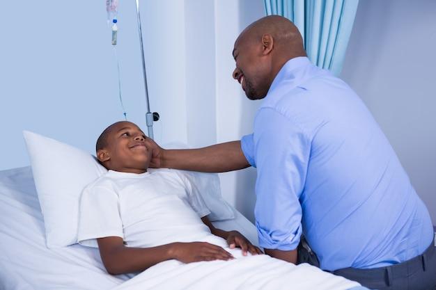 Männlicher arzt tröstet patienten während des besuchs in der station