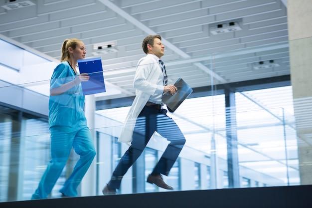 Männlicher arzt und krankenschwester, die mit röntgenbericht im korridor laufen