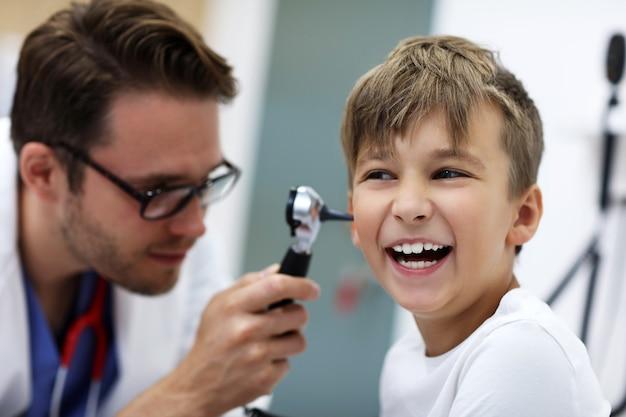 Männlicher arzt untersucht das ohr eines jungen mit einem otoskop