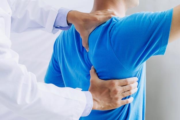 Männlicher arzttherapeut, der die behandlung von verletztem rücken untersucht. rückenschmerzpatient, behandlung, arzt, massage für rückenschmerzen.