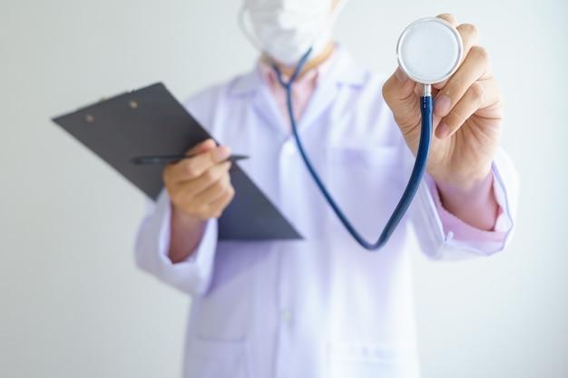 Männlicher asiatischer arzt, der im bürokrankenhaus arbeitet und gesichtsmaske trägt, schützt covid 19-viren.