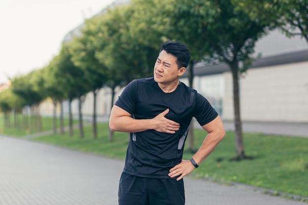 Männlicher asiatischer athlet, hat brustschmerzen, fitness im park und laufen, herzschmerzen nach cardio-training