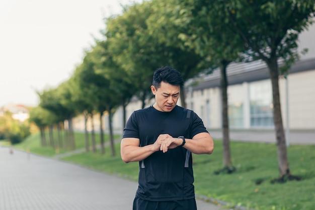 Männlicher asiatischer athlet, müde nach einem morgendlichen joggen, läuft im park in der nähe des stadions