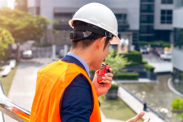 Männlicher asiatischer bauleiter mit walkie-talkie auf der baustelle.