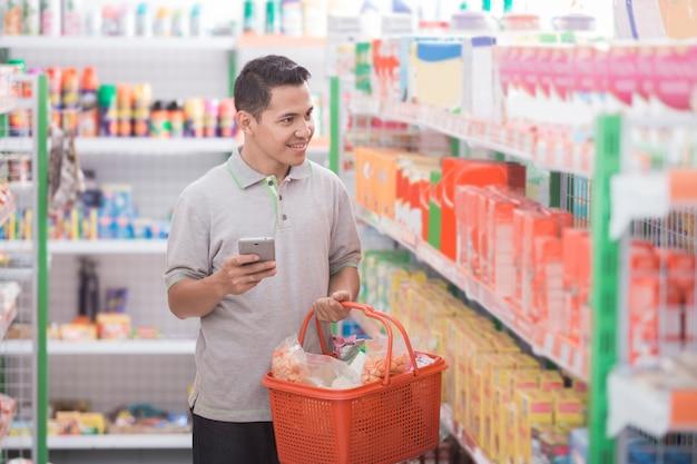 Männlicher asiatischer einkauf am supermarkt
