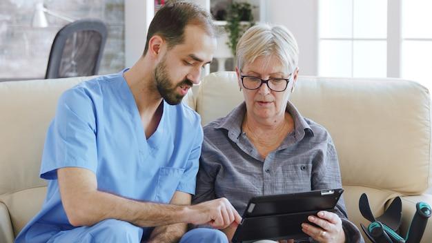 Männlicher assistent, der einer älteren rentnerin beibringt, wie sie ihren tablet-computer im pflegeheim für ihre therapie verwendet