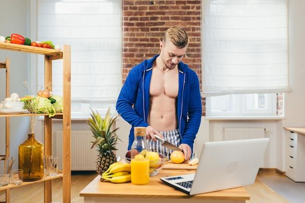 Männlicher athlet bereitet salat und frischen fruchtsaft zu hause in der küche zu