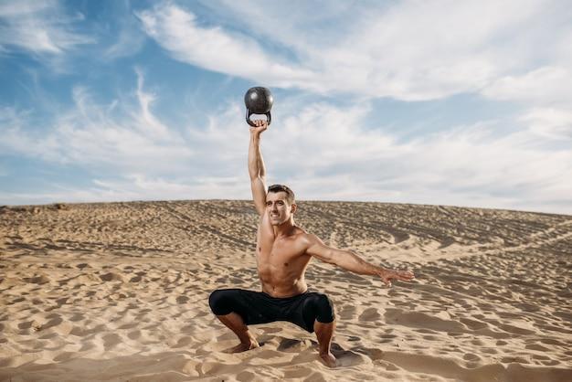 Männlicher athlet, der am sonnigen tag übungen mit gewichten in der wüste macht. starke motivation im sport, krafttraining im freien