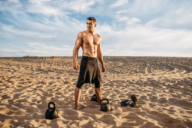 Männlicher athlet, der am sonnigen tag übungen mit hanteln in der wüste macht. starke motivation im sport, krafttraining im freien