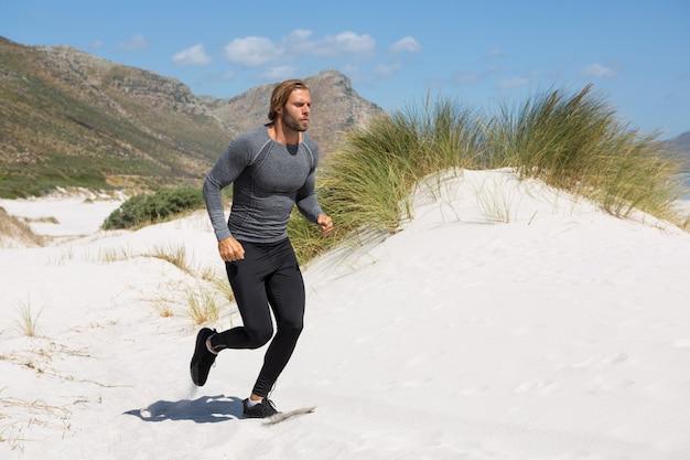 Männlicher athlet, der am strand durch berg läuft
