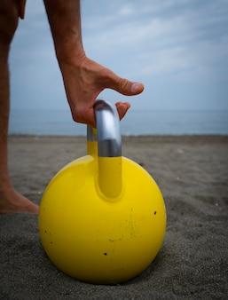 Männlicher athlet, der am strand mit kesselglocken trainiert