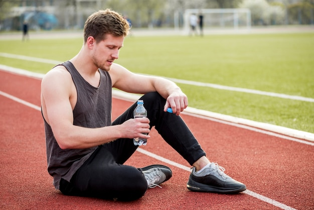 Männlicher athlet, der auf der rennstrecke in der hand hält wasserflasche sitzt