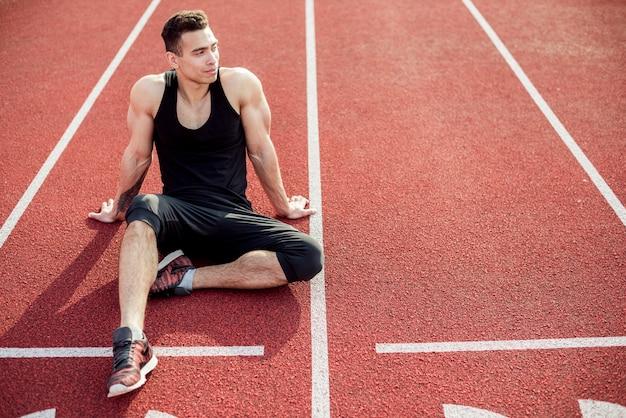 Männlicher athlet, der auf roter rennstrecke sich entspannt