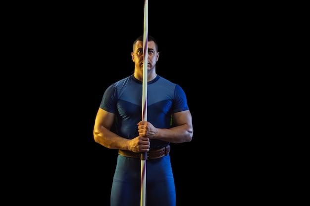 Männlicher athlet, der das werfen des speers auf schwarzem hintergrund im neonlicht übt. profisportler posiert selbstbewusst. konzept des gesunden lebensstils, der bewegung, der aktivität, des wettbewerbs. copyspace.