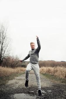 Männlicher athlet der eignung, der auf schotterweg auf dem gebiet läuft