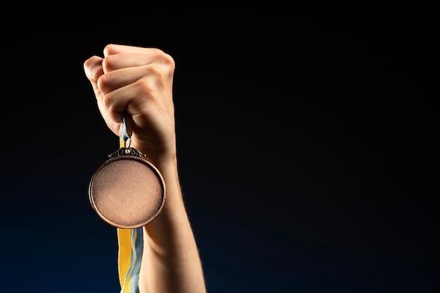 Männlicher athlet, der eine goldmedaille hält