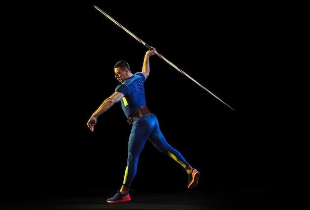 Männlicher athlet, der im werfen speer isoliert auf schwarzem studio im neonlicht übt