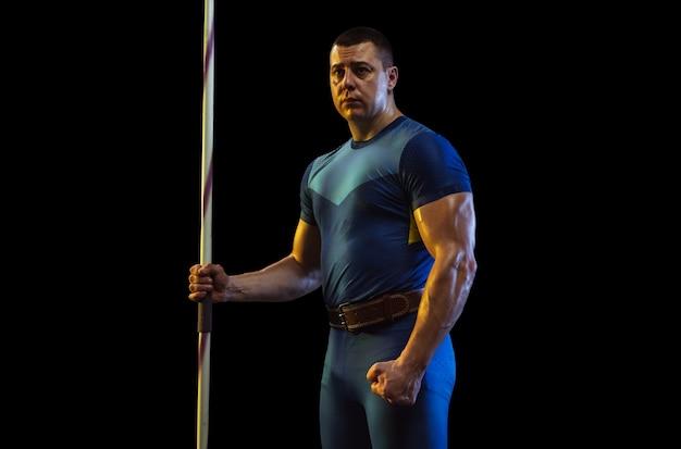 Männlicher athlet, der im wurfspeer auf schwarz im neonlicht übt.