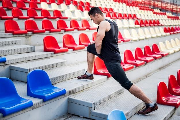 Männlicher athlet, der sein bein auf treppenhaus nahe zuschauertribünen ausdehnt