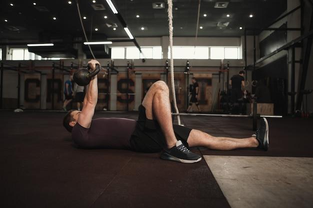 Männlicher athlet, der türkisches kettlebell tut, steht auf und trainiert im cross-fit-fitnessstudio