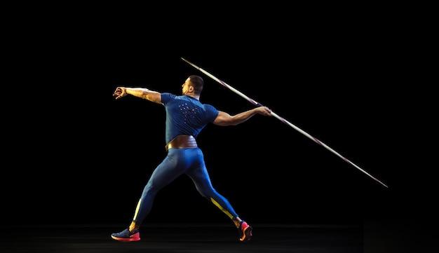 Männlicher athlet, der übt, speer im dunkeln zu werfen