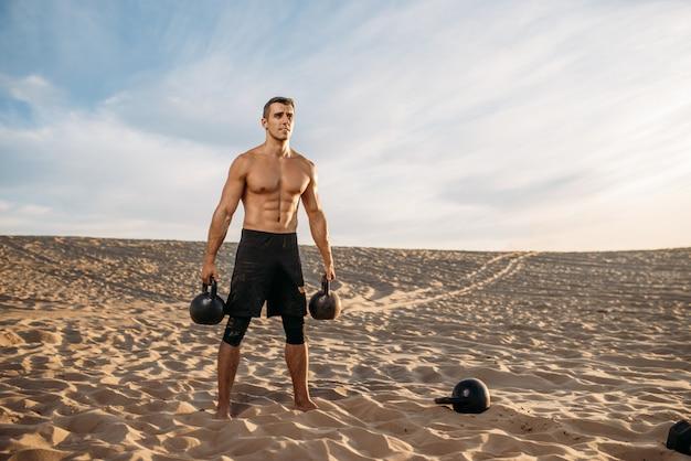 Männlicher athlet, der übungen mit zwei kettlebell in der wüste am sonnigen tag tut. starke motivation im sport, krafttraining im freien