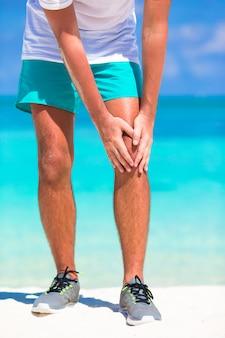 Männlicher athlet, der unter den schmerz im bein beim trainieren auf weißem strand leidet