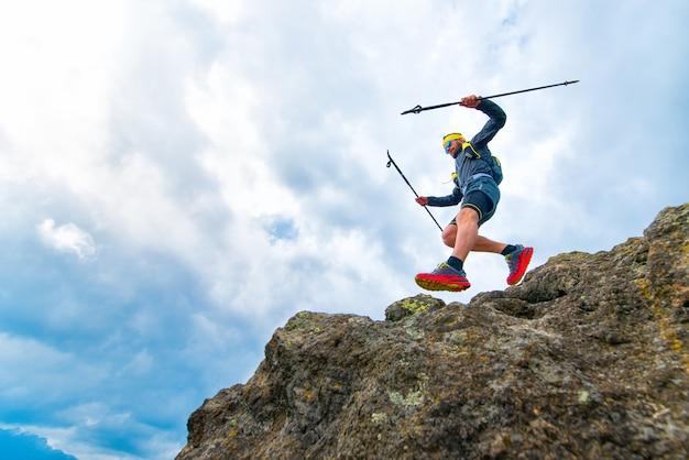 Männlicher athlet fällt von felsigen felsvorsprüngen und praktischem training am gebirgspfad