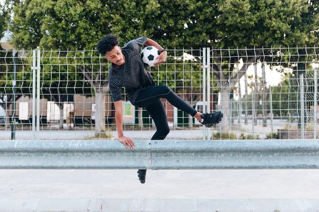 Männlicher athlet in der sportkleidung, die über metallische sperre springt