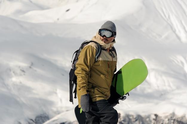 Männlicher athlet mit einem snowboard in den händen steigt auf die strecke