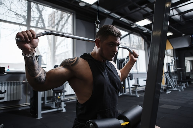 Männlicher athlet mit muskulösem körper, der auf vertikalem rudergerät des lat pulldowns arbeitet