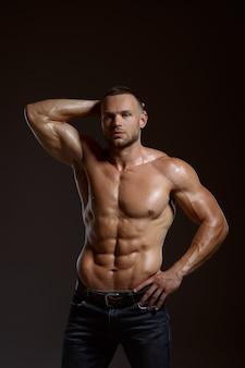 Männlicher athlet mit muskulösem körper posiert im studio