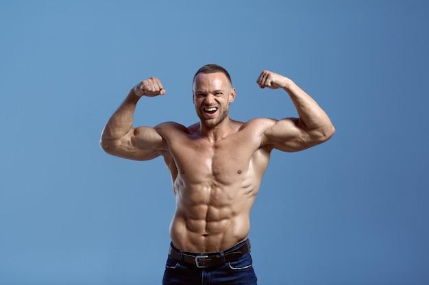 Männlicher athlet mit muskulösem körper zeigt seine kraft