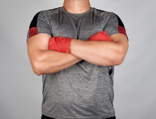 Männlicher athlet verschränkte die arme vor der brust, die bürsten wurden mit einem roten elastischen verband umwickelt