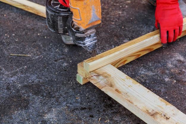 Männlicher auftragnehmer, der mit hölzerner planke und schneider auf dem boden arbeitet