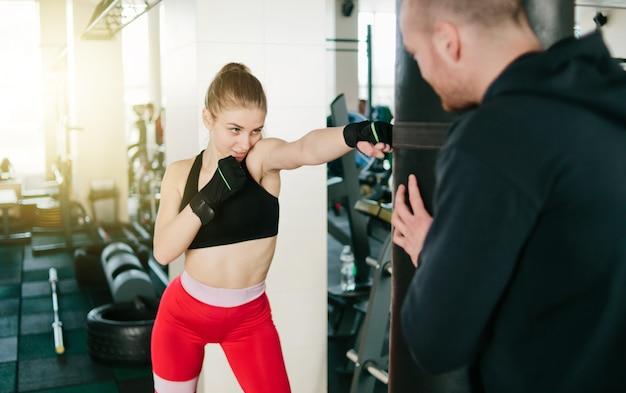 Männlicher ausbilder trainiert junge frau, handschläge am boxsack im fitnessstudio zu tun.