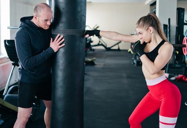 Männlicher ausbilder trainiert junge frau, handschläge am boxsack im fitnessstudio zu tun