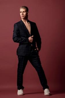 Männlicher ausführender, der elegant in den turnschuhen und im anzug ohne hemd aufwirft